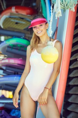Surfer woman posing with surfboard.