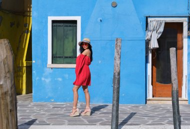 happy tourist woman posing among colorful houses on Burano island, Venice. Tourism in Italy concept