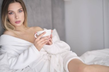 woman in a bathrobe drinks morning coffee in bed