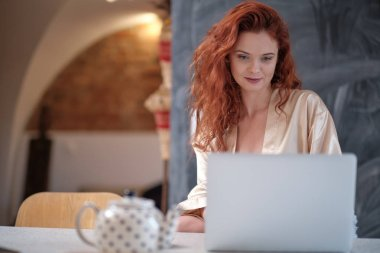 Woman in a bathrobe works on a laptop at home