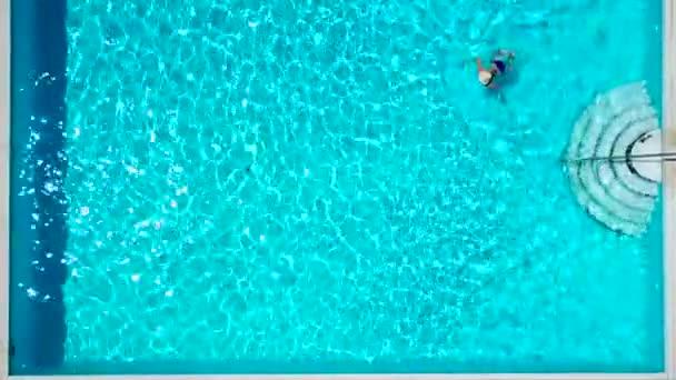 863e55b1d9 Vista dall'alto come una donna in un costume da bagno blu nuota in piscina–  filmato stock