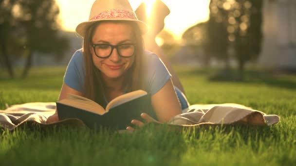 4b3da3e427 Fille à lunettes de lecture livre allongé sur une couverture dans le parc  au coucher du soleil– séquence vidéo