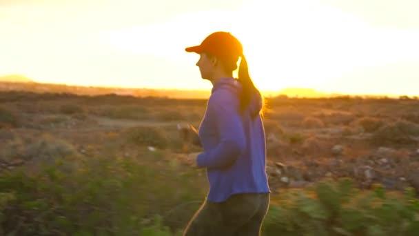 Žena vede podél opuštěné asfaltové silnici při západu slunce, zpět zobrazení. Hory na pozadí. Zpomalený pohyb