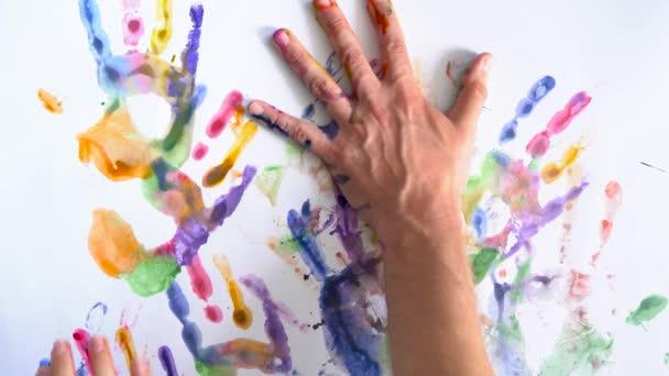 Kreativní koncept - muž a žena se otisky rukou malované na bílém pozadí