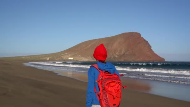 Active hiker woman walks on the beach. Caucasian young woman in red hat with backpack on Tenerife, Canary Islands, Spain