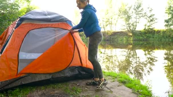 Žena je uvedení turistický stan v lese