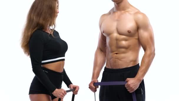 Atletický muž a žena, která dělá biceps cvičení s elastickým pásem na bílém pozadí v studio