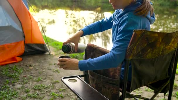 Nő teázás egy karosszékben közelében egy sátor, a folyó partján