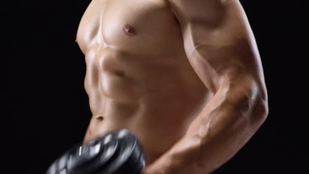 Mann beugt seine Hände mit Hanteln vor und trainiert seinen Bizeps auf schwarzem Hintergrund im Studio
