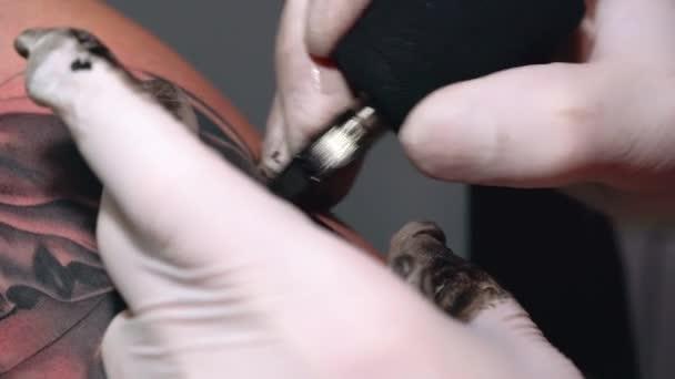 Proces kreslení tetování na mužské ruce v černým inkoustem detail