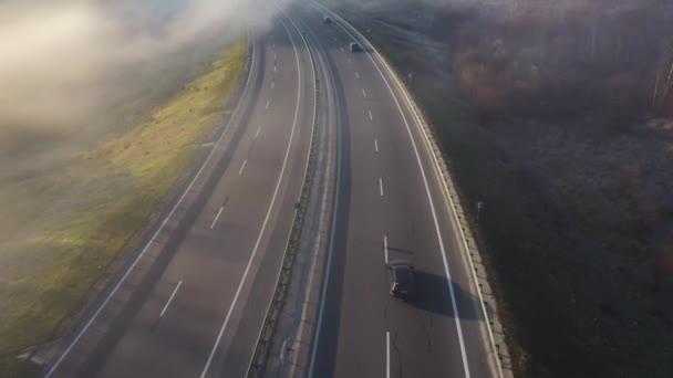 Pohled z výšky na silnici, kdy vozy pohybují. Silnice je zahalena v mlze