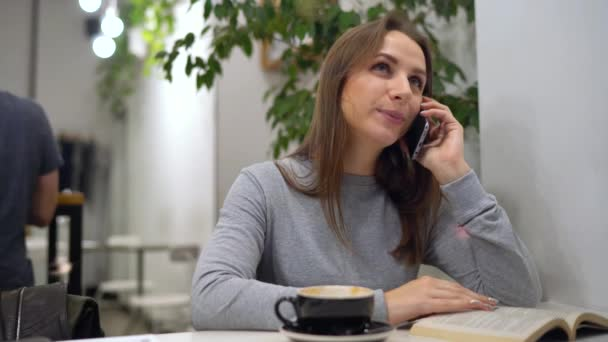 Beautiful woman spends her time in a cafe: reading a book, talking on the phone and drinking coffee