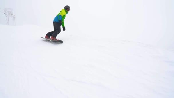 Extrem-Snowboarder fährt frischen Pulverschnee den steilen Berghang hinunter