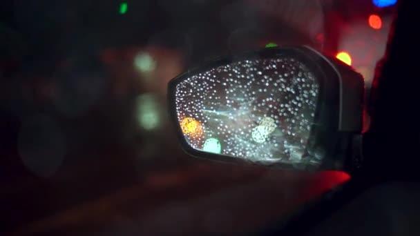 Světla měst vidět na auto zpětné zrcátko v noci, za deště
