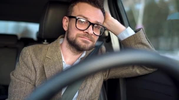 zufriedener bärtiger Mann mit Brille fährt bei sonnigem Wetter Auto die Straße hinunter