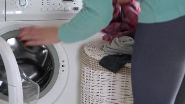Nő betölti a ruhaneműt a mosógép