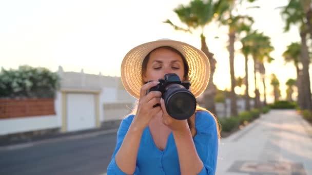 Fotós turista nő fotózni kamerával egy gyönyörű trópusi táj naplementekor