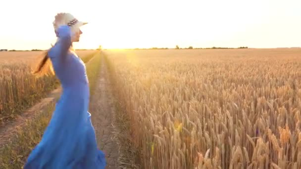 Krásná žena v modrých šatech a klobouk se v západu slunce otáčí uprostřed pšeničné polní. Koncept svobody. Pšeničné pole v Sunset