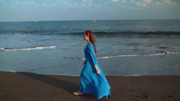 Nő a gyönyörű kék ruhában sétáltam egy fekete vulkáni strand