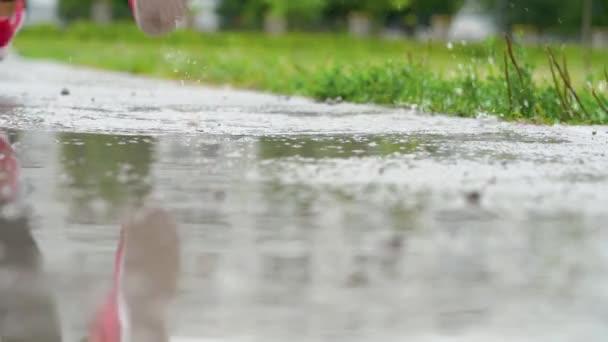 Beine eines Läufers in Turnschuhen. Sportlerin joggt im Freien, tritt in schlammige Pfützen. Ein einzelner Läufer läuft im Regen und macht Spritzer. Rückseite. Zeitlupe