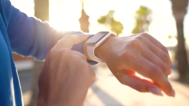 Smartwatch. Woman using smart watch. Closeup of female touching touch screen on watch entering watch app and starts to run