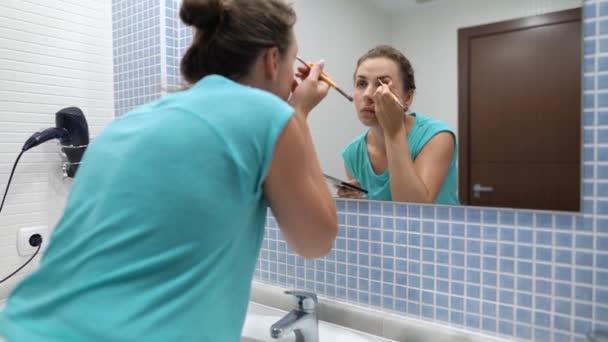 Szép nő nem szemöldök smink szemhéjfesték és sminkkefe előtt fürdőszoba tükör