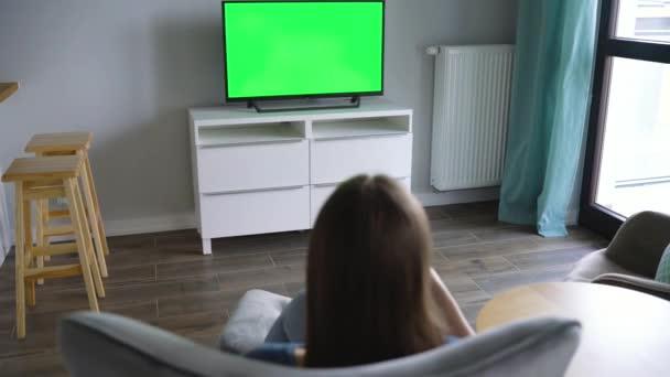 Žena sedí v křesle, dívá se zelenou obrazovkou na televizi a přepíná kanály pomocí dálkového ovládání. Chroma klíč. Interiéru