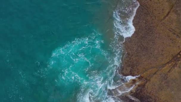 Pohled na pouštní kamenné pobřeží v Atlantickém oceánu. Pobřeží ostrova Tenerife. Vzdušné záběry mořských vln dosahující na břeh
