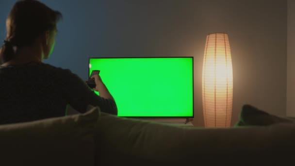 Žena sedí na gauči, dívá se na televizi se zelenou obrazovkou a přepíná kanály dálkovým ovladačem. Chromatický klíč. Indoors