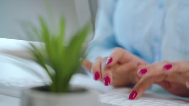 Ženské ruce s jasnou manikúrou psaní na klávesnici počítače