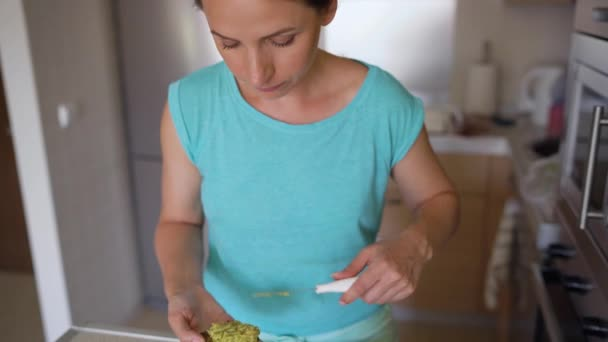Nő főzés avokádó pirítós - rak apróra vágott avokádó teljes kiőrlésű kenyér