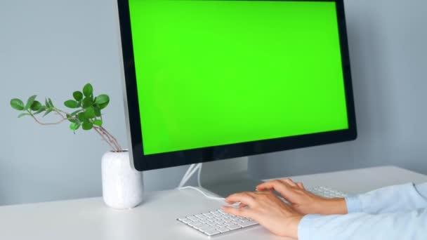 Žena píšící na klávesnici počítače, monitor se zelenou obrazovkou. Chromatický klíč. Kopírovat mezeru.