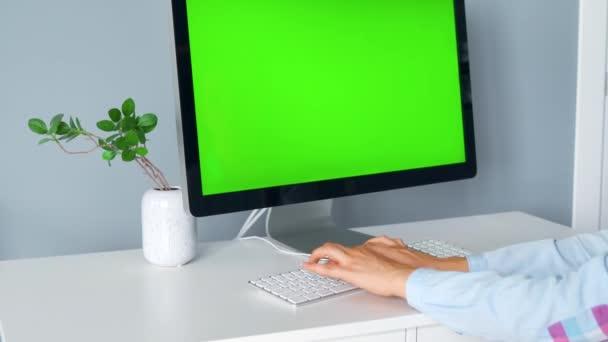 Frau tippt auf Computertastatur, Monitor mit grünem Bildschirm. Chroma-Schlüssel. Kopierraum.