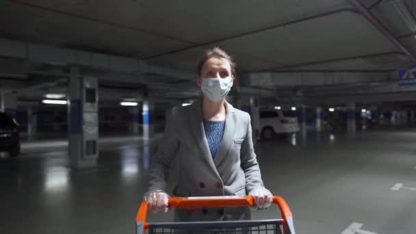 Žena v lékařské masce prochází s vozíkem s potravinami podzemním parkovištěm. Nákup během Covid-19 koronavirus pademia
