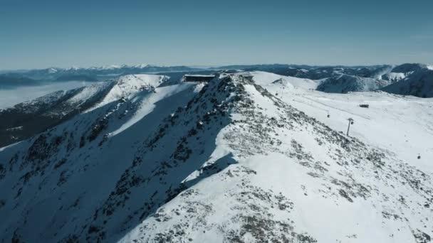 Vzdušný výhled na lyžařské středisko - lanovky, restaurace, lyžaři lyžující na úbočí hory. Vysoké Tatry. Slovensko, Chopok