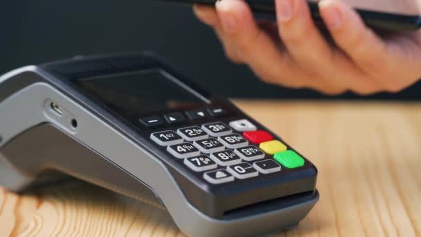 Érintésmentes fizetés okostelefonnal. Vezeték nélküli fizetési koncepció. Közelkép, nő okostelefon készpénz nélküli pénztárca NFC technológia fizetni rendelési banki terminál.
