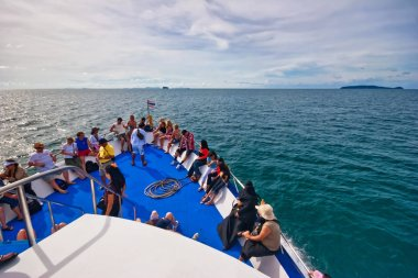 tourists on the top deck of ship sailing from Phuket island to P