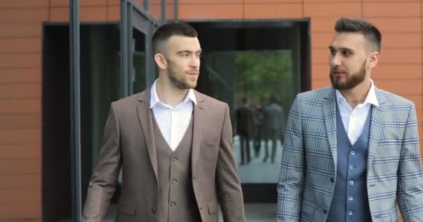 Two businessmen chat together as they walk along through a busy modern office building.