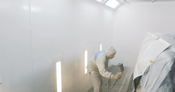 Footage of a car being painted and varnished in a painting chamber Lacquering a black car