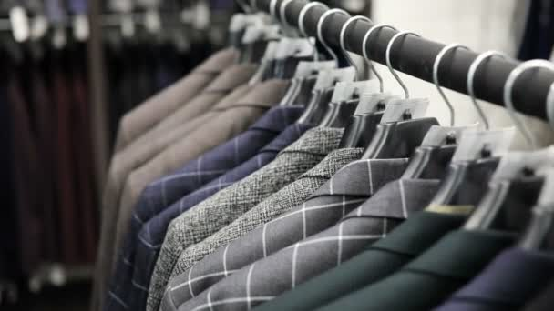 Mens suit at tailors shop. Mens hands choose a jacket in their wardrobe. Male choosing