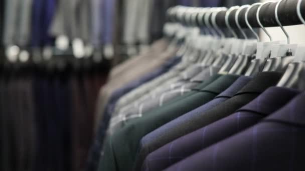 Ramínko Pánské oblečení různých barev na pozadí oblek obchod, detail.