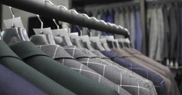 Řada mužů oblek bundy na ramínkách. Kolekce nových krásné šaty na ramínkách v obchodě