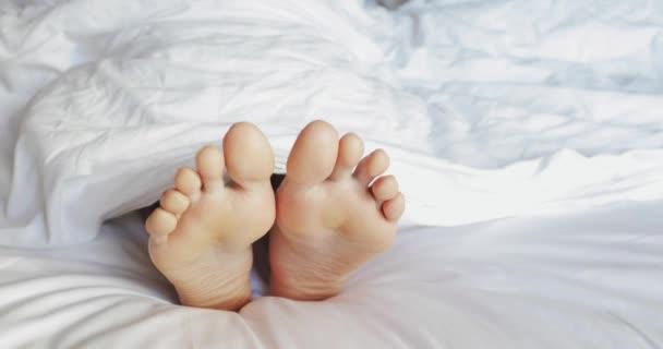 Žena nohy v posteli. Closeup