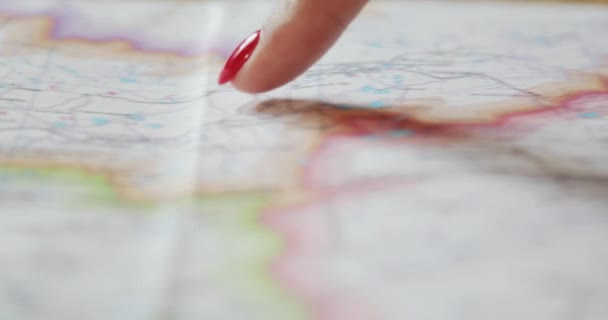 Closeup ženských rukou ukazující na cestovní mapa míst k návštěvě. Dolly záběr Dámské prst plánování