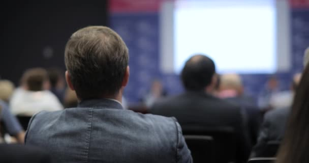 people at a conference or presentation, workshop, master class photograph. the speaker tells the speech at conference. Back view. Business and Entrepreneurship concept.