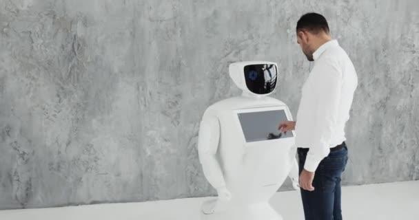 A stílusos ember kommunikál egy robot, megnyomja egy műanyag mechanikus kar, hogy a robot, kézfogás. Kibernetikus rendszer ma. Robotika modern technológia. Humanoid autonóm robot.