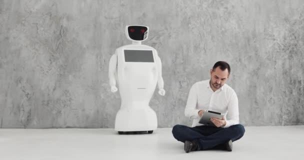 ember, a robot simogatta. barátságot kötött egy robot. Robotika modern technológia. Egy ember kommunikál egy robot,