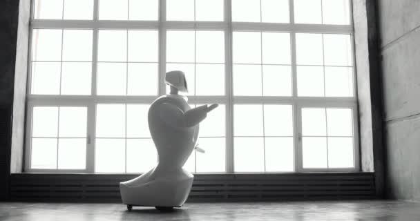 Robotika modern technológia. A robot úgy néz ki, a kamera, az a személy. A robot látható érzelmeket. Vet fel a kezed, tánc vagy felháborodott. Vagy támadás