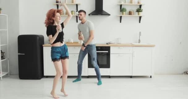 Šťastný mladý pár tančící v kuchyni nosí pyžamo poslechu hudby ráno doma