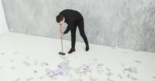 muž v obleku shromažďuje peníze od podlahy